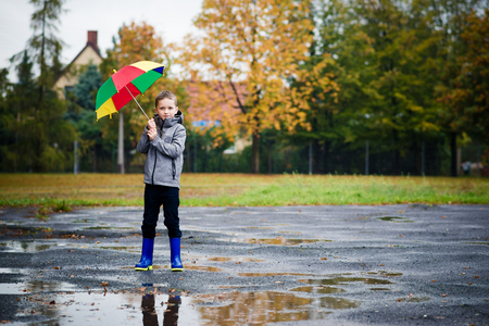 Sad child walking in rubber wellingtons on wet footpath. Rainy autumn day.