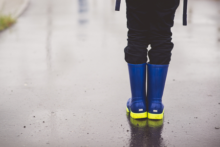 wellingtons: Child standing in rubber wellingtons on wet footpath. Rainy autumn day.