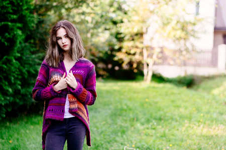 Portrait of a young woman in woolen sweater posing in home garden
