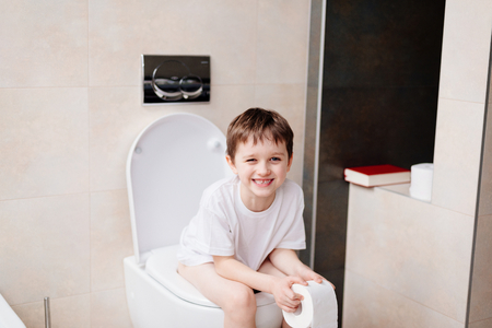 Little 7 years old boy sitting on toilet. Holding white toilet paper Фото со стока