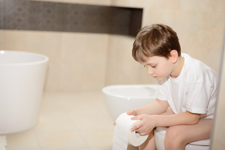 Little 7 years old boy sitting on toilet. Holding white toilet paper Stockfoto