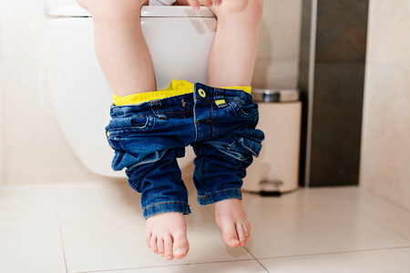 defecation: Little 7 years old boy on toilet. Low view on his legs Stock Photo