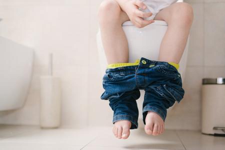 El pequeño niño de 7 años de edad en el inodoro. Vista de la baja en las piernas Foto de archivo