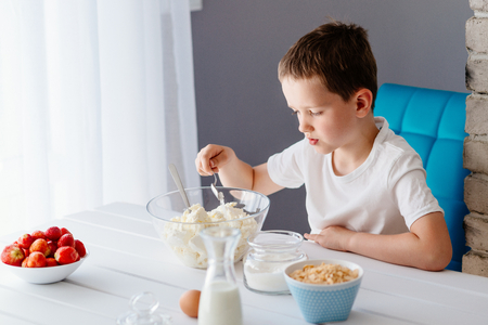 adding sugar: Boy adding sugar to white cheese in bowl for cheesecake. Child helping in the kitchen. Baking with children Stock Photo
