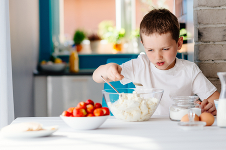 Boy adding sugar to white cheese in bowl for cheesecake. Child helping in the kitchen. Baking with children Stock Photo