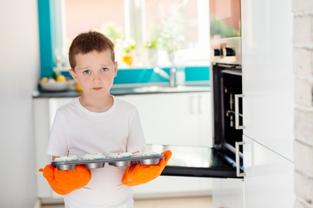 Child holding baking tray with cupcakes. Boy helping in the kitchen. Baking with children Stock Photo