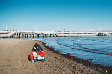 shorelines: Little boy child on the beach. Winter sea Stock Photo