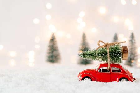 Kleines rotes Autospielzeug, das Weihnachtsbaum im schneebedeckten Miniaturwald trägt Standard-Bild