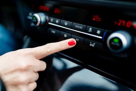 La mujer se enciende el aire acondicionado en el coche. moderno interior del coche