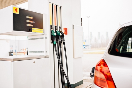 fuelling pump: Small silver car refuelling at the gas station Stock Photo