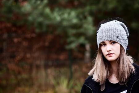 Thoughtful young woman in woolen grey cap in garden.