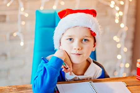 Small baby boy writes a list of gifts for Christmas