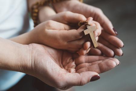 Modlitwa rodzinna. Matka i dziecko ręce z drewnianym różańcem