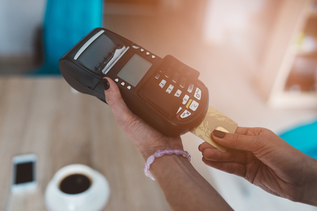 Customer pays by credit card at the cafe