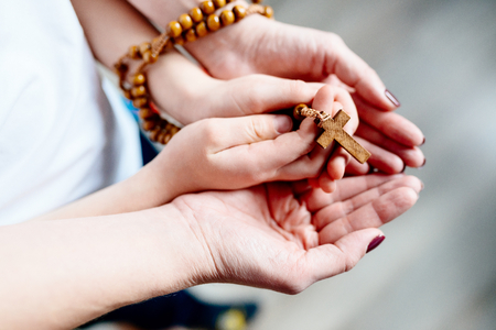 Family prayer. Mother and child hands with wooden rosary