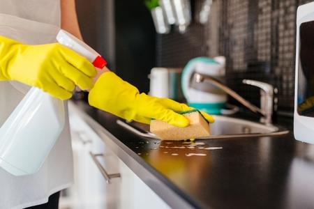 La mujer que limpia muebles de cocina con esponja y limpiador en aerosol. Más de esta serie en mi cartera Foto de archivo - 68273204