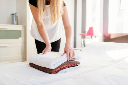 Young hotel maid placing fresh towels on a bed. MORE FROM THIS SERIES IN MY PORTFOLIO