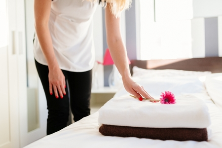 Young hotel maid placing flower on fresh towels on a bed. MORE FROM THIS SERIES IN MY PORTFOLIO