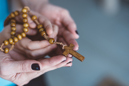 Mother and child praying together. Holding rosary in hand. More from this series in my portfolio