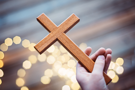familia orando: Little boy child praying and holding wooden crucifix. More from this series in my portfolio Foto de archivo