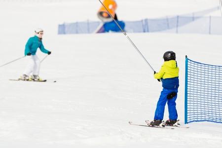 kids at the ski lift: Child on a ski lift going uphill. Child in ski school in winter resort.