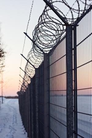 antiterrorist: Sharp barbed wire on fence at cold winter