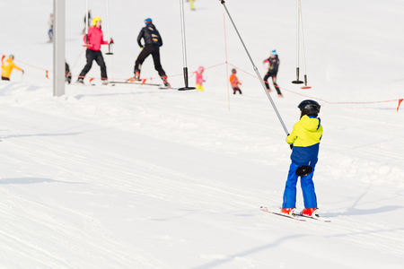 kids at the ski lift: Child on a button ski lift going uphill. Child in ski school in winter resort.