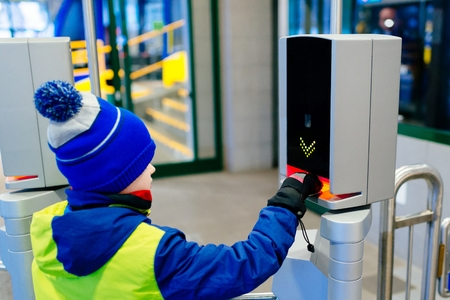 Child validating a ticket in railway or underground entrance. Crosses the turnstile Stock Photo