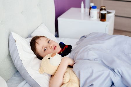 sickbed: Sick child hugging a teddy bear in bed.