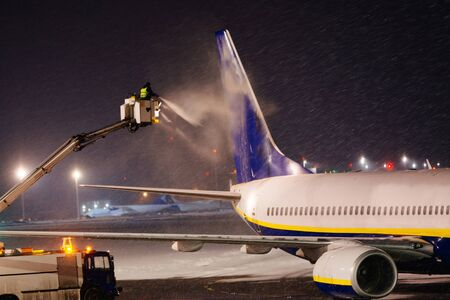 Deicing passenger plane with glycol at night