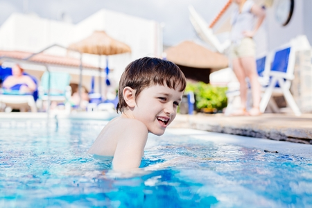 Happy child playing in hotel pool. Tenerife. Canary Islands Stock Photo