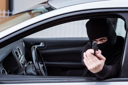 Man in black balaclava with handgun driving a car. Car thief, car theft