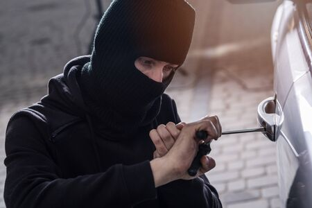 looting: Auto thief in black balaclava trying to break into car with screwdriver. Car thief, car theft