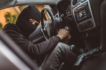 robo de autos: Car thief trying to start car with screwdriver in ignition. Car thief, car theft