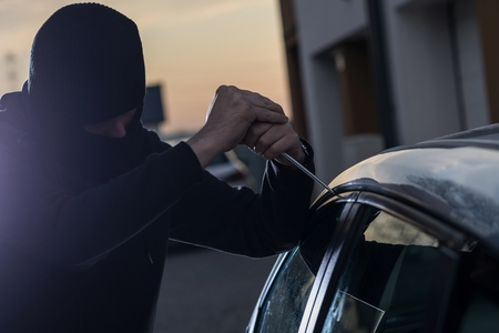 robo de autos: ladrón de automóviles en pasamontañas negro que intenta penetrar en un coche con un destornillador. ladrón de coches, el robo de automóviles