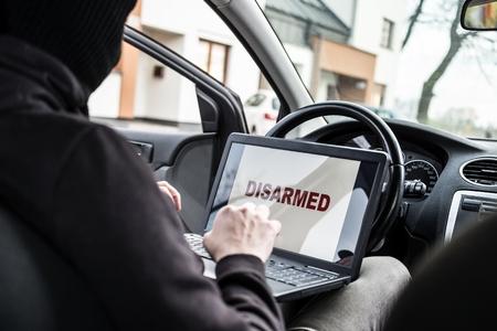 robo de autos: Car thief trying to break car security systems with laptop computer. Car thief, car theft