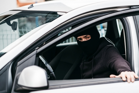 Auto thief in black balaclava closing door of stolen car. Car thief, car theft Stock Photo