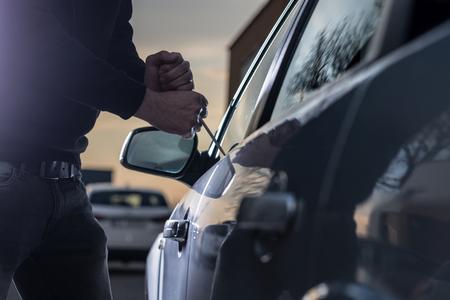 Auto dief in zwarte balaclava proberen in te breken in de auto met een schroevendraaier. Autodief, autodiefstal Stockfoto