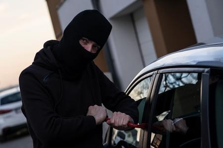 robo de autos: Auto thief in black balaclava trying to break into car with crowbar. Car thief, car theft