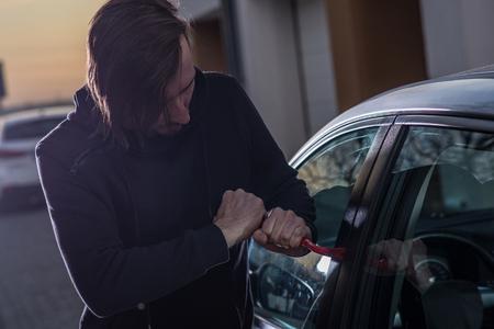 robo de autos: ladrón de automóviles en pasamontañas negro que intenta penetrar en coche con la palanca. ladrón de coches, el robo de automóviles