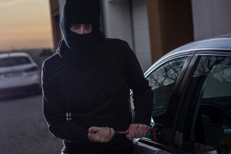 looting: Auto thief in black balaclava trying to break into car with crowbar. Car thief, car theft