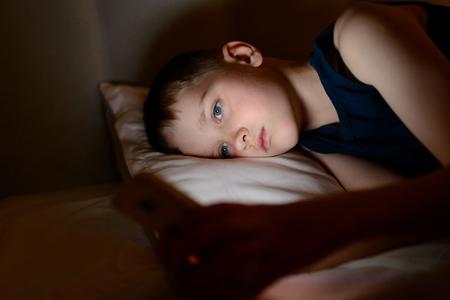 7 歳の子供男の子夜ベッドでスマート フォンを使用して 写真素材