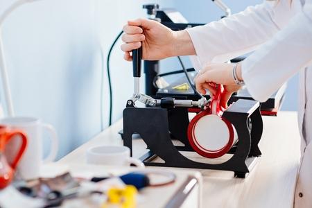 Woman making thermal transfer print on white mug 스톡 콘텐츠
