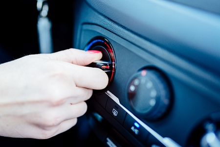 Woman regulates heating in her car. Modern car interior Banco de Imagens - 72397922