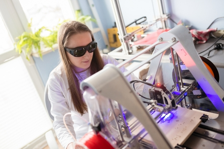 Woman in white lab coat and protective glasses working with laser engraver
