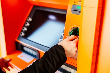 Woman slides a credit card into ATM Stock Photo