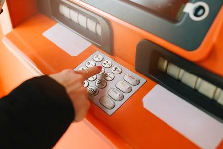 automatic transaction machine: Mujer que ingresa el código pin en el teclado del cajero automático Foto de archivo
