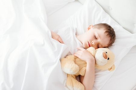 nightwear: Little boy child sleeping in bed. Hugging his favourite teddy bear. Covered with white duvet