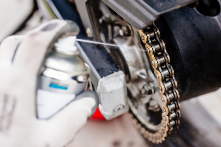 Lubricating motorcycle chain with dedicated chain spray grease 스톡 콘텐츠