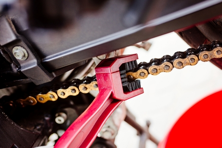 Cleaning motorcycle chain with dedicated chain brush Stock Photo